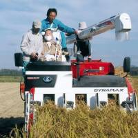 Shigeru Matsumoto (front right), a farmer with ALS, rides a combine in a rice paddy in Ogata, Akita Prefecture, in October 2010. His journal was published after his death in 2015. | RUI MATSUMOTO / VIA KYODO