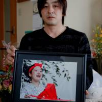 Go Kasai, father of Rima Kasai who killed herself, poses with his daughter's picture at his house during an interview in Fujisaki, Aomori Prefecture, in February. | REUTERS
