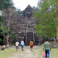 Tourists walk up to Preah Vihear, an ancient cliff-top temple that Cambodia and Thailand have sporadically fought over for more than a century, on March 29. | KYODO