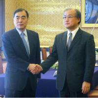 Japan's Deputy Minister for Foreign Affairs Takeo Akiba and his Chinese counterpart Kong Xuanyou shake hands at the start of their meeting in Tokyo on Tuesday. | KYODO