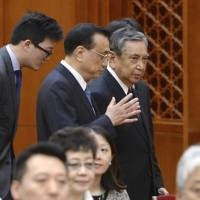 Chinese Premier Li Keqiang (center) talks to Yohei Kono, head of the Japanese Association for the Promotion of International Trade, before their meeting Monday at the Great Hall of People in Beijing. | AP