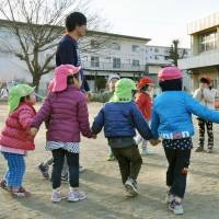 Male day care workers play with children in the city of Chiba on Feb. 8. | KYODO