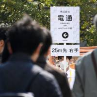 Dentsu investors head to an emergency shareholders meeting March 30 in Tokyo. | KYODO