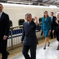 Spain's King Felipe (left), Queen Letizia (third left), and Emperor Akihito (second left) and Empress Michiko smile to well-wishers as they board a shinkansen to depart on a one-day trip to Shizuoka from Tokyo Station on Friday. | POOL / REUTERS