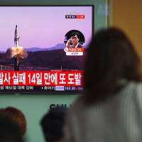 People in a train station in Seoul on Wednesday watch file footage of a North Korean missile launch.   AFP-JIJI