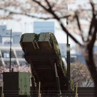A launch unit for PAC-3 surface-to-air missiles, used to engage incoming ballistic missiles, is seen through cherry blossoms at the Defense Ministry in Tokyo on Wednesday.   AFP-JIJI