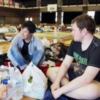 Foreign students chat in a gymnasium used as an evacuation shelter in Kumamoto on April 17 last year, following a series of powerful earthquakes in the region. | KYODO