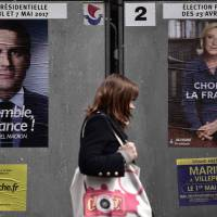 A pedestrian walks past posters of French presidential election candidates in Paris on Friday. Japanese investors, worried about French political risks, are keeping the country's bonds at arm's length. | AFP-JIJI