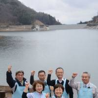 Takeo Fukaya (right), president of Omofuru Heart, poses with his staff at Lake Fujinuma in Sukagawa, Fukushima Prefecture, which is now filled with water after being empty for six years since the 2011 Great East Japan Earthquake. | FUKUSHIMA MINPO