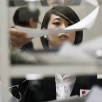 A woman puts her company's financial reports on a shelf for media outlets at the Tokyo Stock Exchange's press club in Tokyo in November 2011. | KYODO