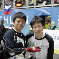 Masahiro Kasuya (right) poses with 'pilot' Kazuya Maeda, who wears a prosthetic hand he developed, during Cybathlon 2016, the first international competition of robotic technologies for people with disabilities, in Switzerland in October. | MELTIN MMI CO.