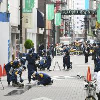 Police officers investigate the scene of daylight robbery on fashionable Suzuran Street in the middle Tokyo's bustling Ginza district on Friday afternoon. | KYODO