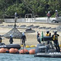 Bagged stones were laid on to the shores of the Henoko area in Okinawa Prefecture on Tuesday as the government began constructing seawalls for a replacement facility for a new U.S. base. | KYODO