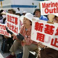 Demonstrators stage a sit-in in front of the U.S. Marines' Camp Schwab in Nago, Okinawa Prefecture, on Tuesday to protest the construction of sea walls at a planned replacement facility for the U.S. Air Station  Futenma. | KYODO