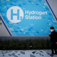 A passer-by walks in front of a hydrogen station in Tokyo on April 24. The government is betting heavily on hydrogen as a fuel of the future. | REUTERS