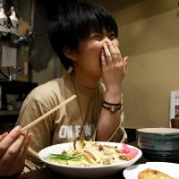 A customer reacts as she eats an 'insect tsukemen' — ramen noodles topped with fried worms and crickets — at Ramen Nagi in Tokyo. | REUTERS