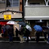 People line up Sunday in front of Negi Ramen in Tokyo for a one-day event that featured 'insect tsukemen' noodles. | REUTERS