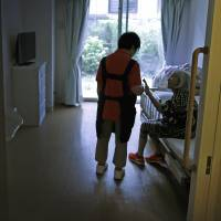 A 65-year-old caregiver chats with a nursing home resident in the Kasai district in Edogawa Ward, Tokyo, last June 30. | BLOOMBERG
