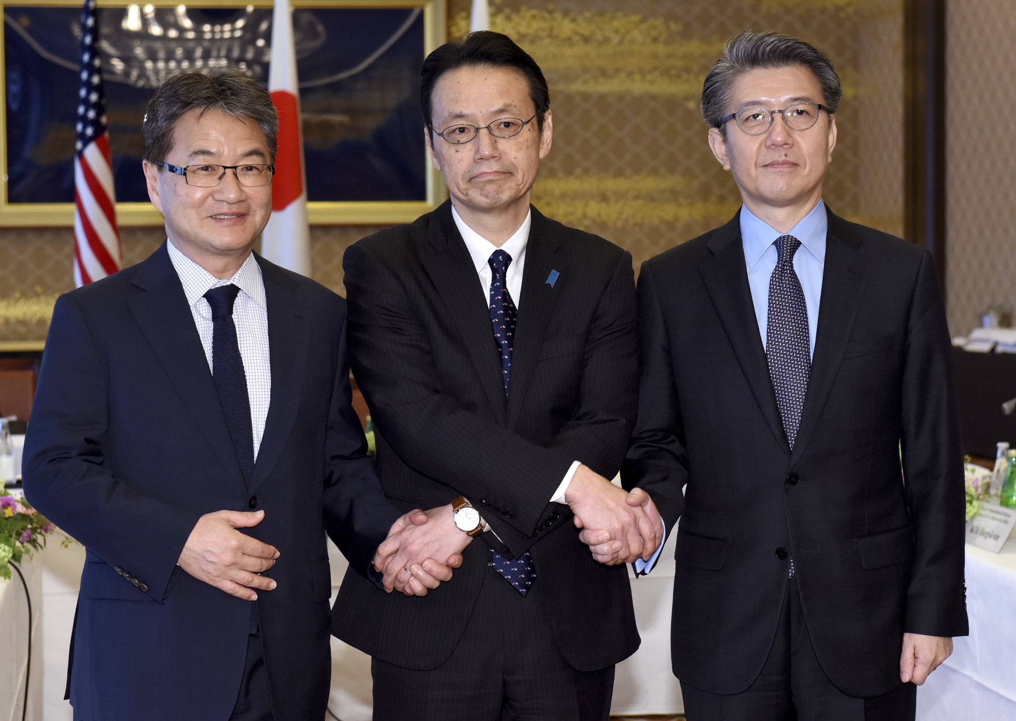 Joseph Yun (from left), U.S. special representative for North Korea policy, Kenji Kanasugi, director-general of the Foreign Ministry's Asian and Oceanian Affairs Bureau, and Kim Hong-kyun, special representative for Korean Peninsula peace and security affairs at the South Korean Foreign Ministry, join hands before their meeting about North Korean issues at the Iikura Guesthouse in Tokyo on Tuesday. | AP