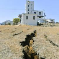 A large crack that split the ground at Kyoto University's volcanological research center after last year's earthquake is seen in the village of Minamiaso, Kumamoto Prefecture, on April 4. | KYODO