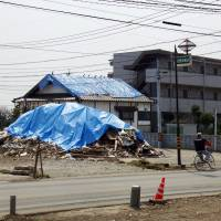 A destroyed house in the town of Mashiki, Kumamoto Prefecture, is covered in blue construction tarps on March 30. | DAISUKE KIKUCHI