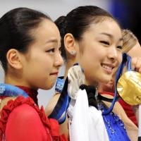 Mao Asada (left), with tears in her eyes, holds her silver medal next to South Korea's Yuna Kim, who won the gold, at the Vancouver Winter Olympics in February 2010. | KYODO