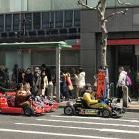 People dressed in Nintendo video game characters drive go-karts in Tokyo on April 2. | MAGDALENA OSUMI