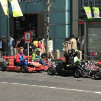 Tourists are seen driving rented MariCar go-karts in Shibuya Ward, Tokyo, on April 2. | MAGDALENA OSUMI