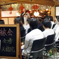 A Buddhist monk at Tenryuin Temple in Tokyo's Taito Ward speaks to young people about marriage during a matchmaking event last November.   KYODO
