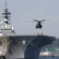 A helicopter lands on the decks of the Izumo, a Maritime Self-Defense Force's helicopter carrier, at Yokosuka base in Kanagawa Prefecture in December. In the first such operation during peacetime under Japan's revised national security laws, the Izumo will escort a U.S. warship in Japanese waters.   REUTERS