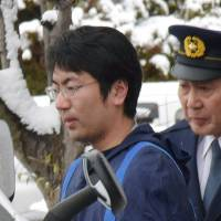 Former NHK reporter Yasutaka Tsurumoto, who is suspected of committing multiple rapes, is escorted by police in February in Yamagata Prefecture. | KYODO