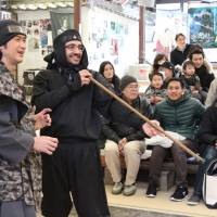 Rishabh Malik, a 27-year-old from India, tries a blowgun shot on Feb. 25 during a demonstration at the Ninja Museum of Igaryu in Iga, Mie Prefecture. | KYODO