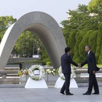 Prime Minister Shinzo Abe and former U.S. President Barack Obama shake hands at Hiroshima Peace Memorial Park during Obama's visit to the atomic-bombed city last May. | AP / VIA KYODO