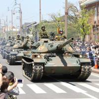 The 14th brigade of the Ground Self-Defense Force runs its tanks during a parade in the city of Zentsuji in Kagawa Prefecture on Sunday. KYODO