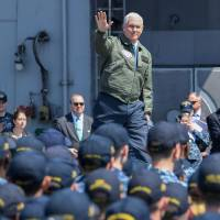 U.S. Vice President Mike Pence waves during a visit to the USS Ronald Reagan aircraft carrier at the U.S. Naval base in Yokosuka, Kanagawa Prefecture, on Wednesday. | AFP-JIJI