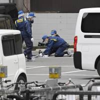 Police Thursday investigate the parking lot in Fukuoka's Tenjin district where a man was robbed of ¥384 million. | KYODO