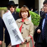 Artist Megumi Igarashi, known as Rokudenashiko (Good-For-Nothing Girl), holds up a sign in front of the Tokyo High Court last Thursday showing the court's decision finding her guilty of obscenity for distributing 3-D scans of her genitalia. | DAISUKE KIKUCHI