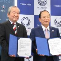 Akira Shimazu (left), CEO of the organizing committee for 2019 Rugby World Cup, and his Tokyo 2020 counterpart Toshiro Muto show off their collaboration agreement signed Wednesday in Tokyo. | KYODO