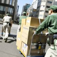 Drivers are being overworked as delivery firms struggle to cope with the boom in online shopping. | KYODO