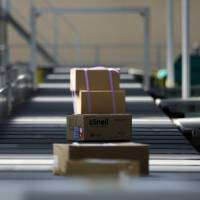 Parcels move along a conveyor at a sorting facility run by Yamato Global Express Co., a subsidiary of Yamato Holdings Co., near Haneda airport in Tokyo in 2014. | BLOOMBERG