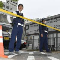 Police officers seal off a road near a parking lot in the city of Fukuoka where around ¥380 million ($3.5 million) in cash was allegedly stolen from a businessman on Thursday. | KYODO