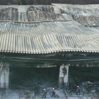 Firefighters examine Askul Corp.'s fire-ravaged warehouse in Miyoshi, Saitama Prefecture, on Feb. 22 before the blaze was fully extinguished. | KYODO