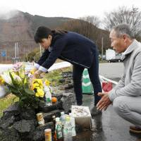 Shinobu and Takuya Yamato lay flowers April 8 near the collapsed Aso Ohashi Bridge in Minamiaso, Kumamoto Prefecture, where their son is believed to have died in last year's deadly earthquakes. | KYODO