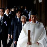A group of lawmakers including Liberal Democratic Party member Hidehisa Otsuji are led by a Shinto priest as they visit Yasukuni Shrine in Tokyo on Friday. | REUTERS