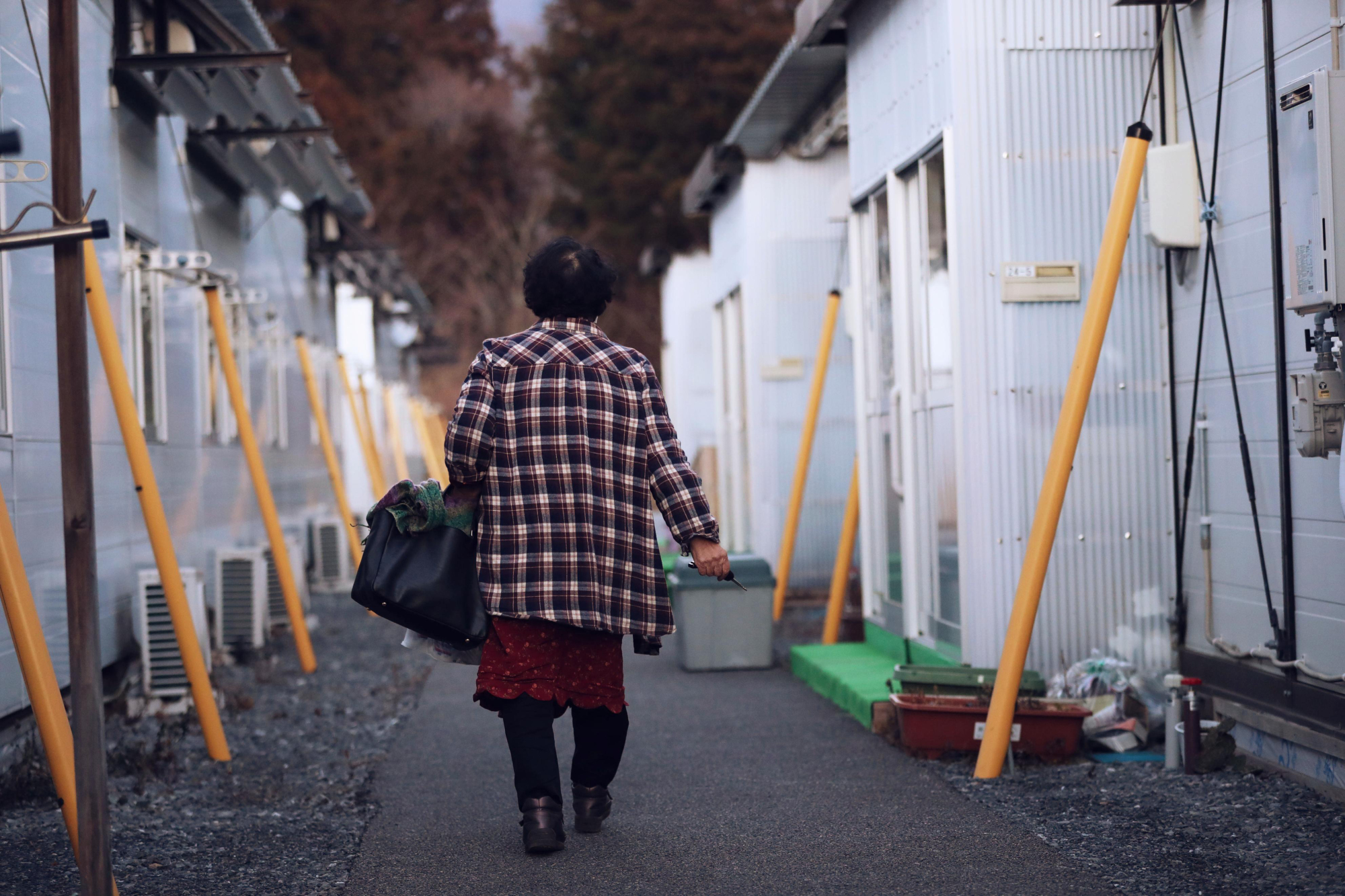 The long stopgap: A woman visits her son, who is still living in temporary housing in Ofunato, Iwate Prefecture. | KYODO