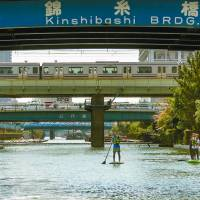 Paddle boarders take to the waters of Yokojuken River in Tokyo. | ROB GILHOOLY