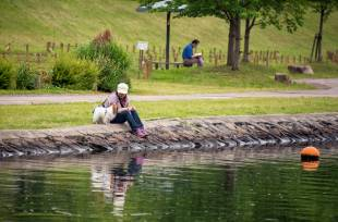 A woman plays with her dog on the banks of a river in Tokyo's Koto Ward.