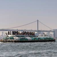 Tourists enjoy the view from atop the Hotaluna water bus in Tokyo. | ROB GILHOOLY