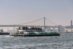 Tourists enjoy the view from atop the Hotaluna water bus in Tokyo.