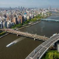 A river cruiser travels down the Sumida River in Tokyo.  | ROB GILHOOLY